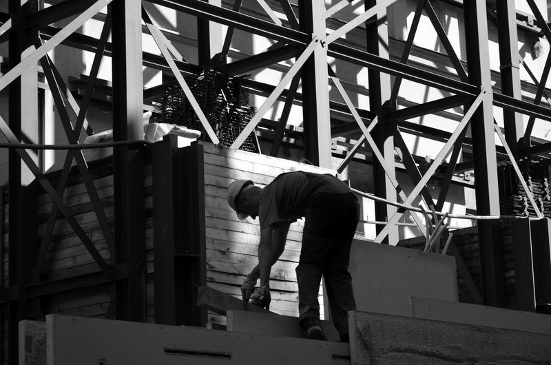 Rear view of man working on metal structure