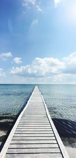 Pier Leading Towards Sea Against Sky