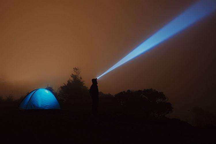 Silhouette man on illuminated field against sky at night