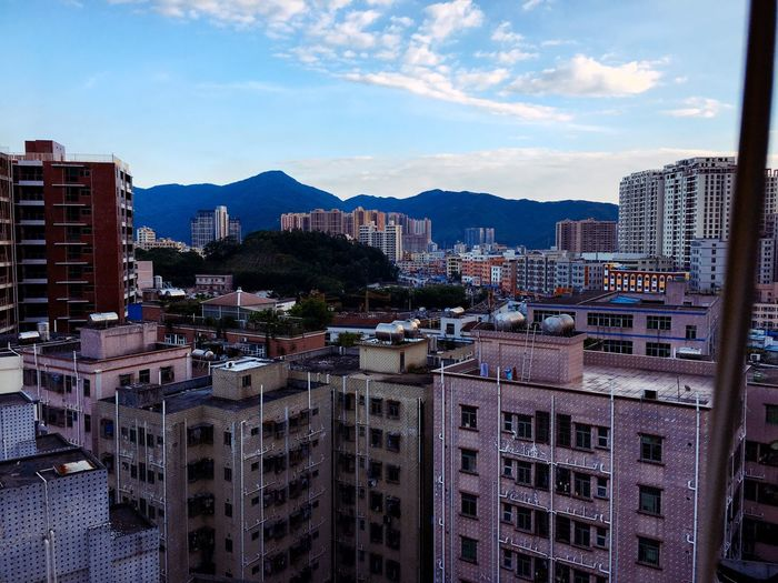 Residential District By Mountains Against Sky