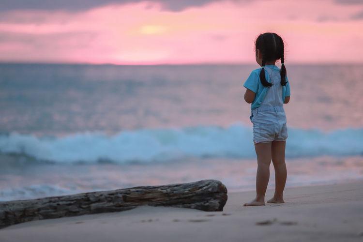 Full length of girl standing at beach during sunset