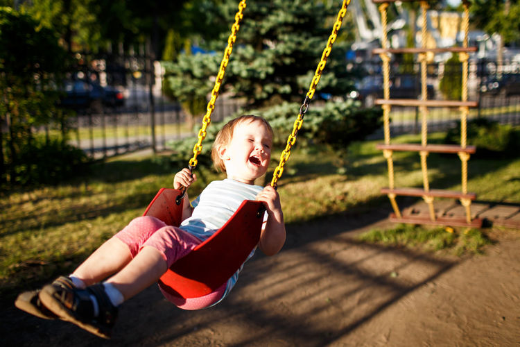 Cute girl swinging in park during sunny day