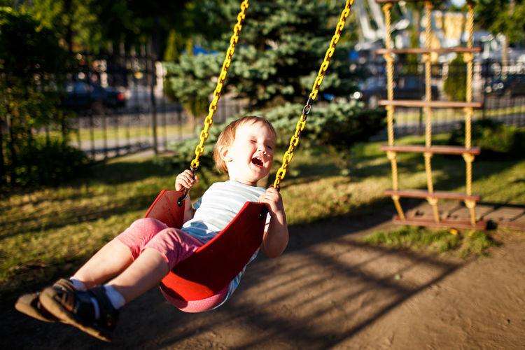 Full length of girl on swing at park during sunny day