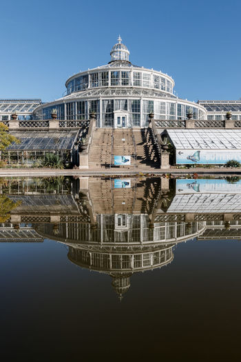 The palm house in the botanical garden. Reflecting Pool First Eyeem Photo Dome Butterfly House Palm House Water Surface Reflections In The Water Botanical Garden City Glass Building Blue Sky No People Day Glass House Symmetry Reflection Architecture My Best Photo Built Structure Building Exterior Clear Sky