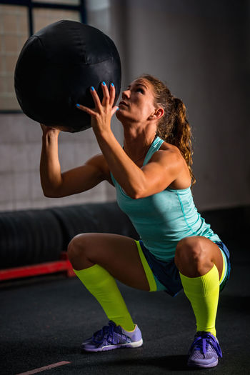 Side View Of Woman Holding Ball In Gym