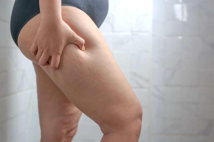 Midsection of woman sitting on wall at home
