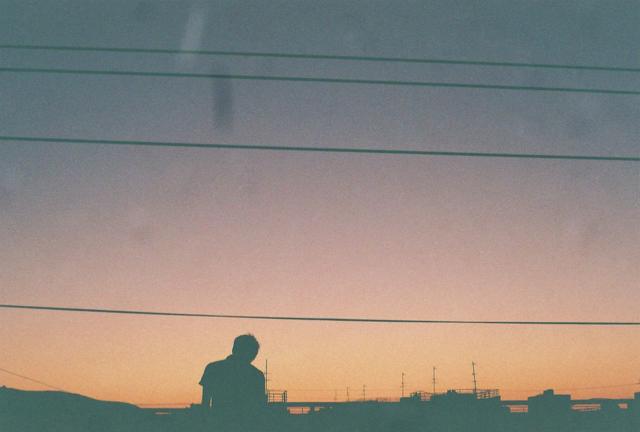 cable, silhouette, connection, power line, sunset, power supply, technology, outdoors, electricity, sky, real people, one person, nature, low angle view, electricity pylon, building exterior, telephone line, architecture, day, people