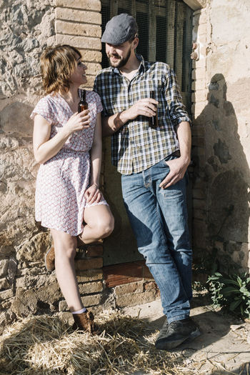 Couple with beer bottles leaning on brick wall