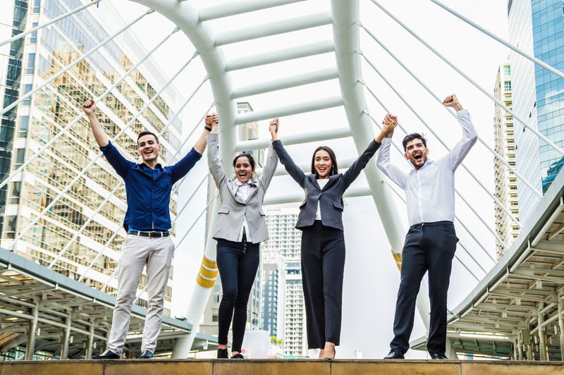 Successful business team on the city background. Achievement Adult American Angle Arms Background Banner Beauty Buildings Built Business Businessman Candid Caucasian City Confidence  District Education Elégance European  Expertise Expressing Exterior Fashion Female Fist Full Glad Hand Happiness Image Intelligence Jump Leadership Life Lifestyles Male Men People Photo Student Study Success Teach Team Tutor Victory Win Women Work