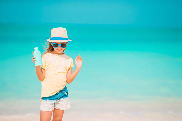 Midsection of woman wearing sunglasses standing by sea