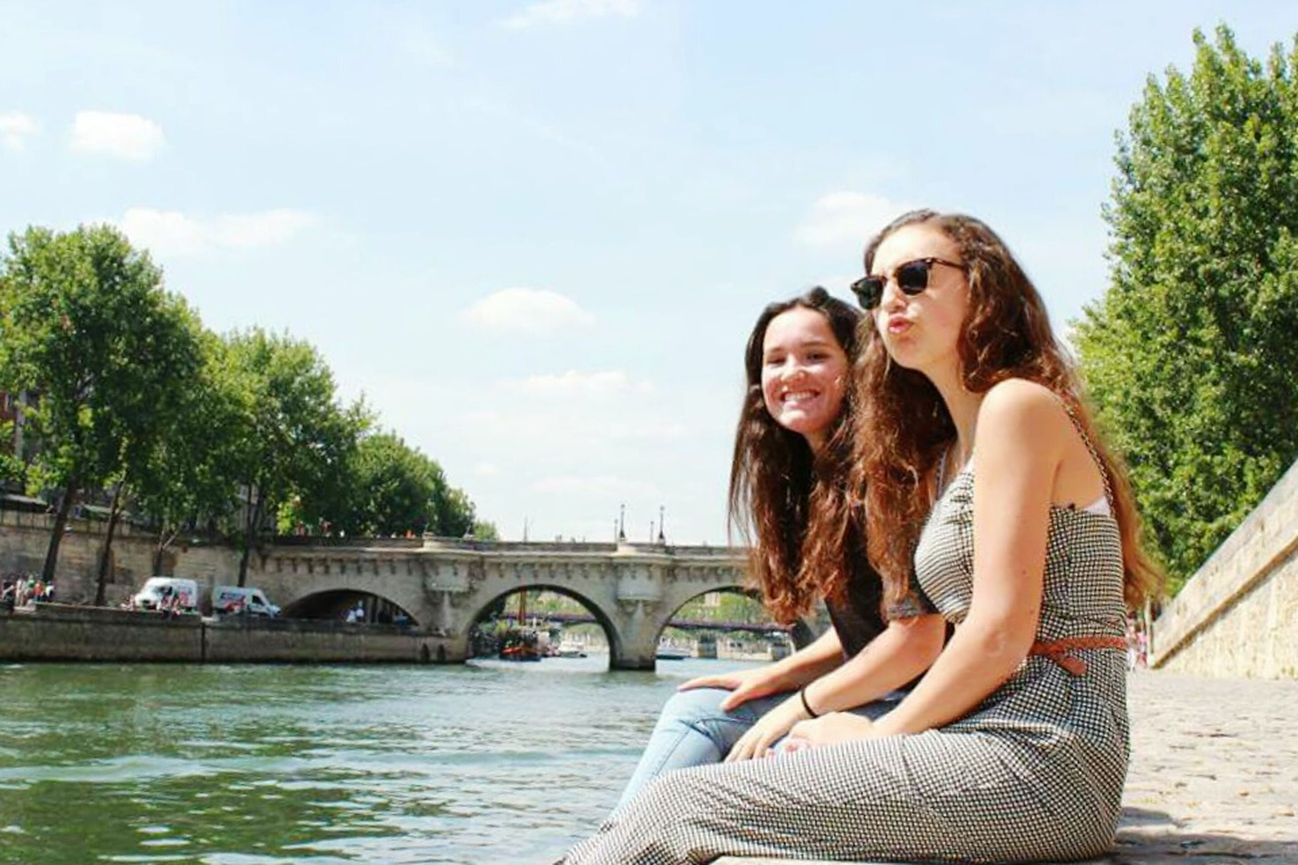 young adult, young women, water, person, lifestyles, leisure activity, casual clothing, looking at camera, tree, smiling, portrait, sunglasses, full length, sitting, sky, long hair, river, happiness