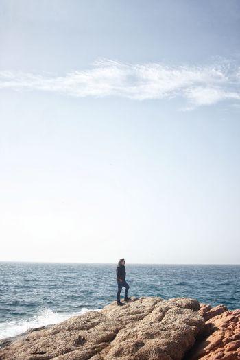 Man standing on rock looking at sea against sky