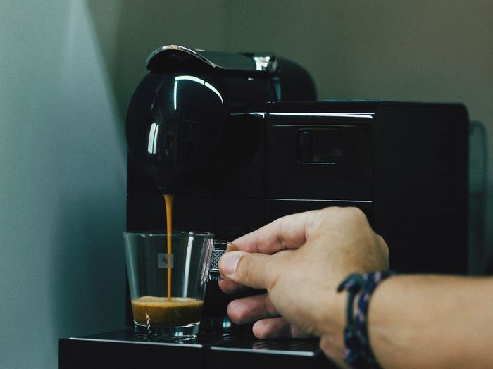Cropped hand of man holding cup by espresso maker