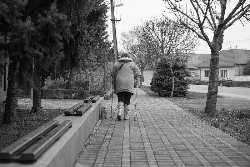 Rear view of man using crutch while walking on sidewalk