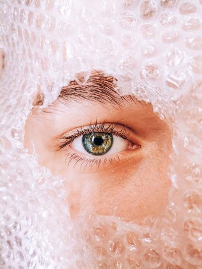Close-up portrait of boy peeking through hole in bubble wrap