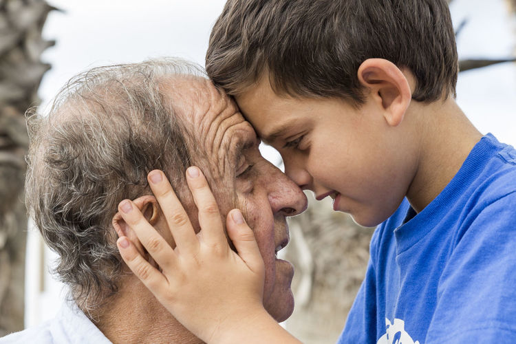 Side View Of Smiling Boy Holding Grandfather