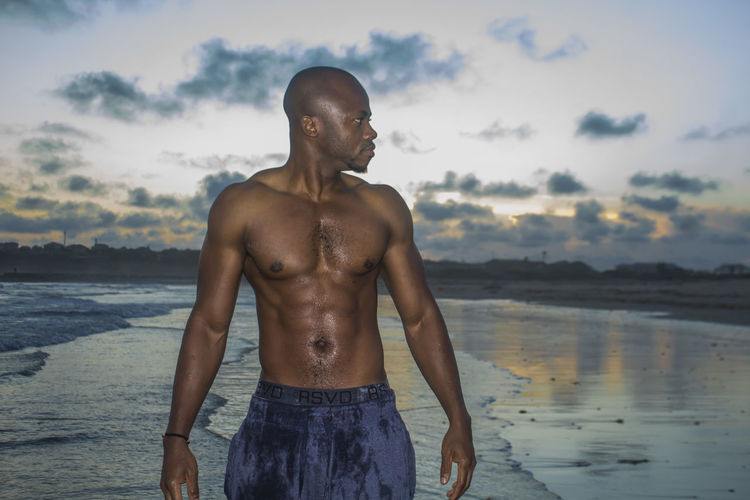 Shirtless man standing at beach against sky