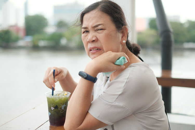 Portrait of senior woman holding drink while sitting outdoors