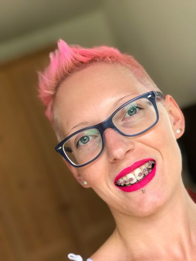 Close-up portrait of smiling woman wearing braces and eyeglasses at home
