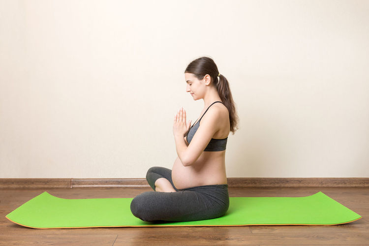 Full length of woman sitting on floor