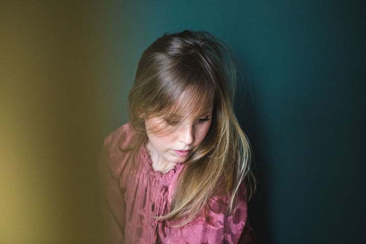 Portrait of girl against wall