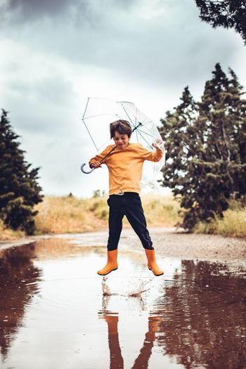 Full length of man standing on wet glass against sky