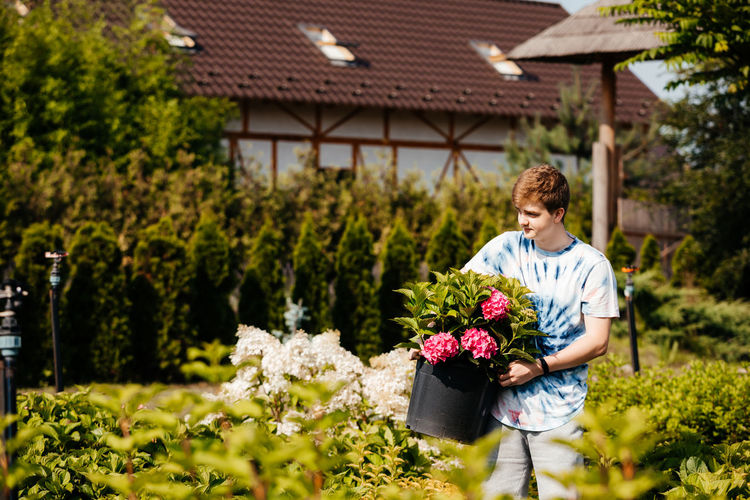 Man holding flowering plant outdoors