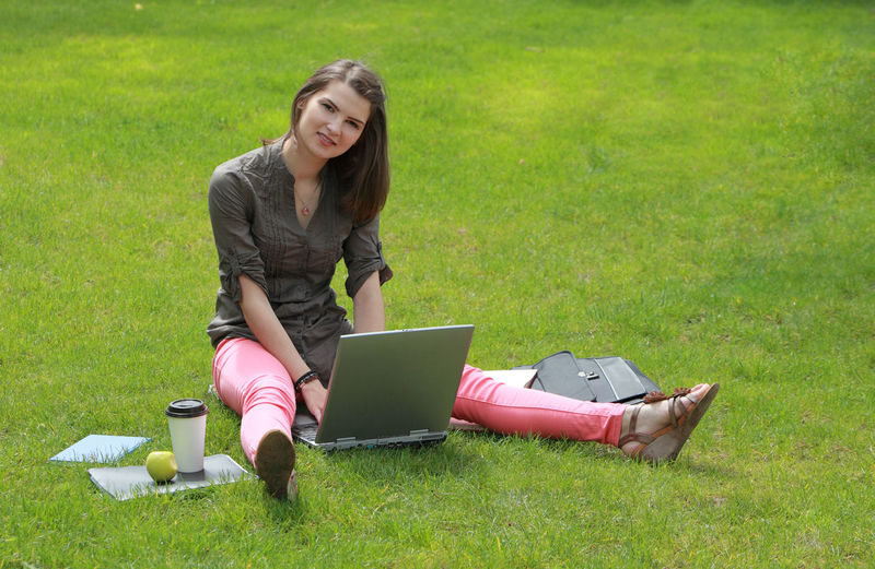 Young woman with a laptop outside in the grass in an urban park. Laptop Wireless Technology Using Laptop Grass Computer Technology Smiling Looking At Camera Portrait One Person Connection Young Adult Sitting Adult Casual Clothing Happiness Beautiful Woman Woman Young Woman Student Outdoors Working On A Laptop Learning
