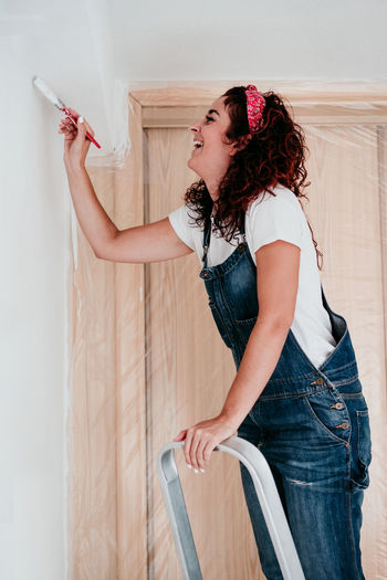 Woman looking away while standing against wall at home