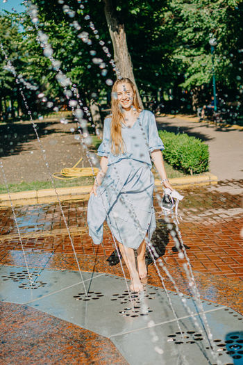 Portrait of young woman standing by fountain at park