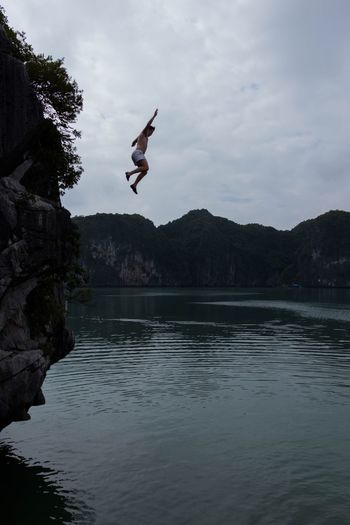 Cliff Cliffs Clif Jumping Jump Jumpshot Falling Water Surface Sea And Sky Brave Vietnam Young Men White Shorts Mid-air Sky Outdoors Summer Traveling Experimental