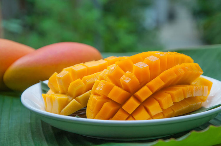 Mango slice on white plate with banana leaf and two yellow - orange color mangoes fruit on banana leaf Green Bowl Close-up Day Focus On Foreground Food Food And Drink Freshness Grass Green Color Healthy Eating No People Outdoors Slice Mangoes White Plate With Food Yellow