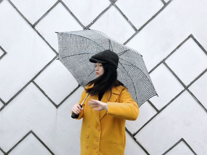 Portrait Umbrella Rainy Days Wall Real People One Person Standing Lifestyles Leisure Activity Pattern Architecture Young Adult Outdoors