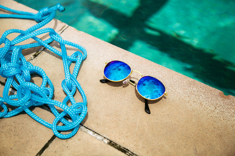 High angle view of rope by sunglasses at poolside