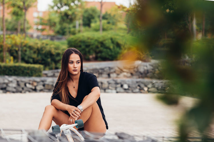 Young woman looking away while sitting on footpath