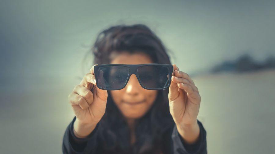 Close-up woman holding sunglasses