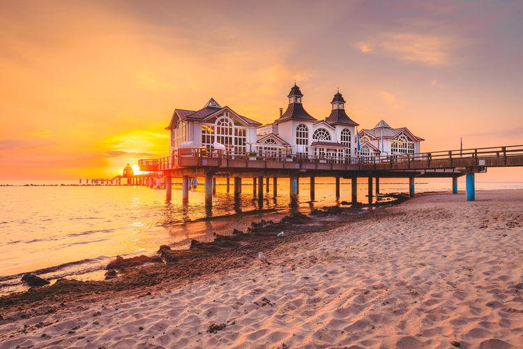 Resort at seashore against sky during sunset