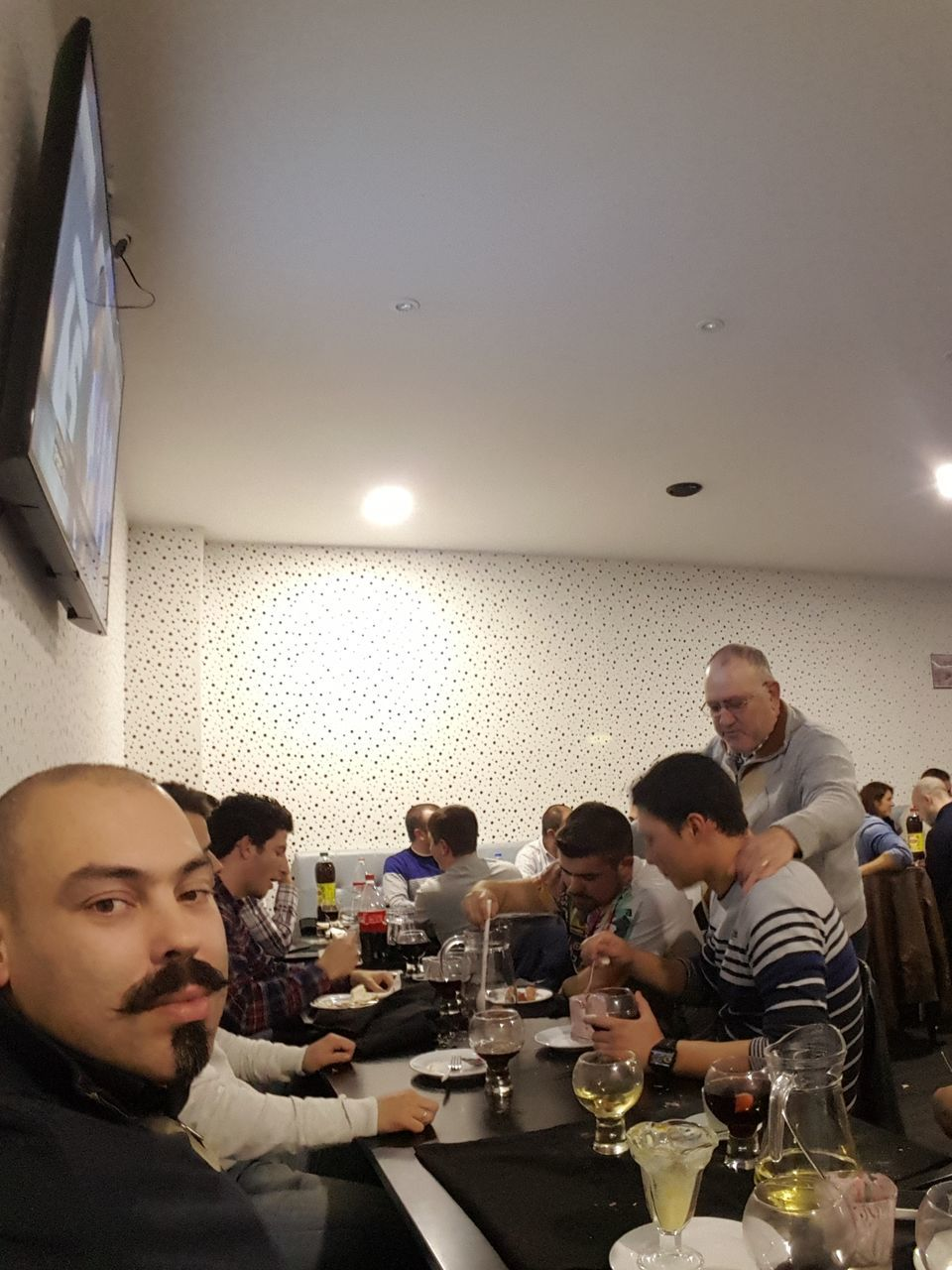 real people, indoors, food and drink, table, restaurant, mid adult men, sitting, leisure activity, togetherness, lifestyles, drink, young men, casual clothing, illuminated, wine, men, food, young adult, large group of people, friendship, alcohol, wineglass, young women, day, adult, people