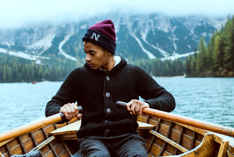 Young Man Rowing Boat On Lake Against Mountains