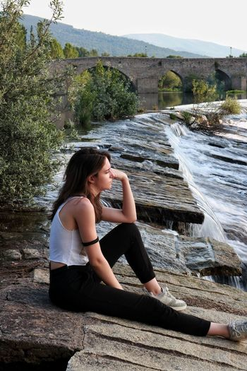 Side View Of Thoughtful Young Woman Looking Away While Sitting By Flowing Water