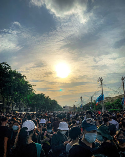 People on street in city against sky during sunset