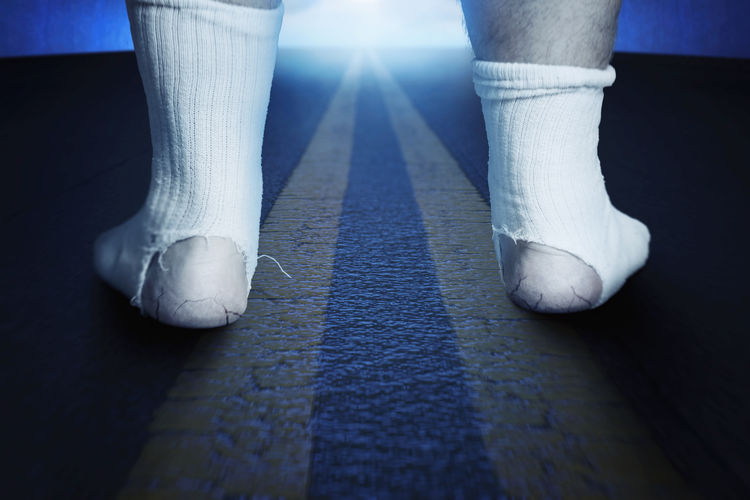 back of standing feet with white socks and a big hole standing on asphalt at night Low Section Human Leg Socks Back Awkward Asphalt Road Tunnel Night Close-up Standing Worn Shabby Hole Homeless Feet Damaged Walking Torn Lifestyle