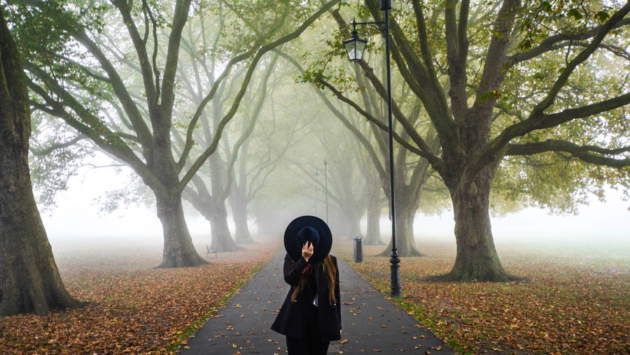 Woman Covering Face With Hat While Standing On Road Amidst Trees During Foggy Weather