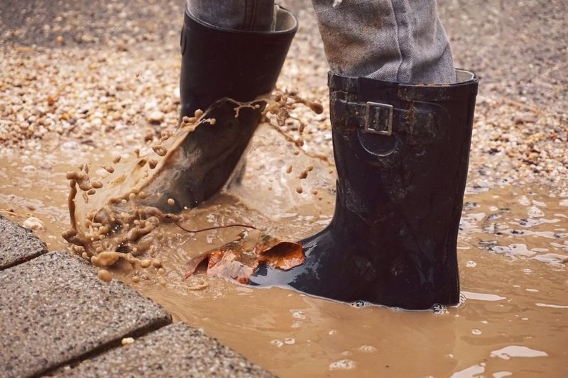 Low Section Of Person Standing In Dirty Puddle