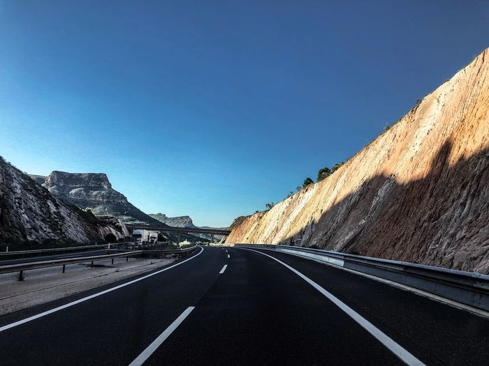 Road Transportation Sky Direction The Way Forward Symbol Clear Sky Road Marking Marking Sign Nature No People Asphalt Copy Space Diminishing Perspective Mountain Blue vanishing point Beauty In Nature Day