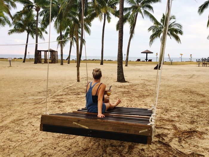 Rear view of woman sitting on wooden swing at beach
