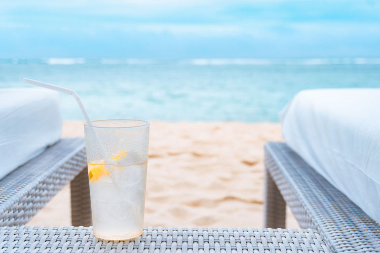 Close-up of drink on table at beach against cloudy sky