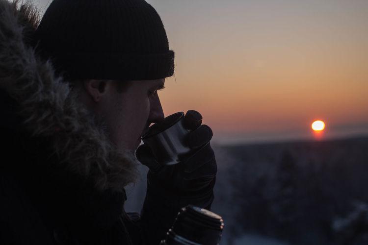 Man drinking during sunset