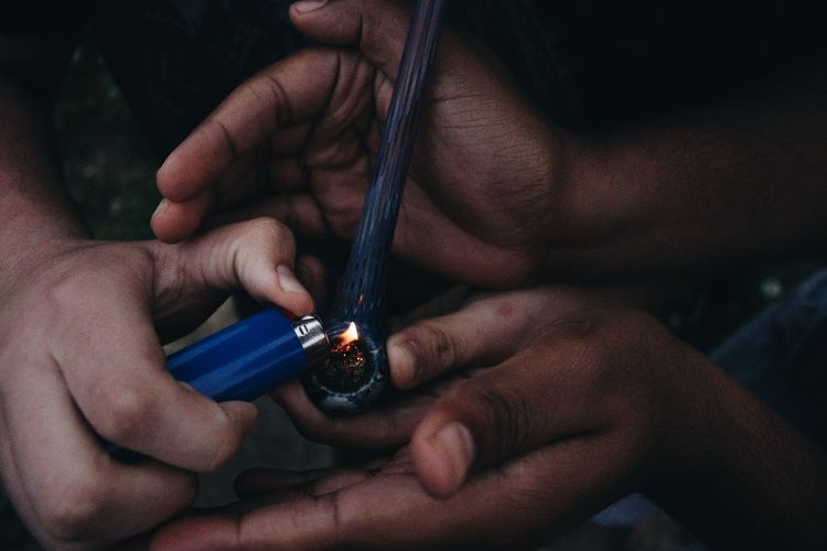 Cropped image of friends lighting smoking pipe