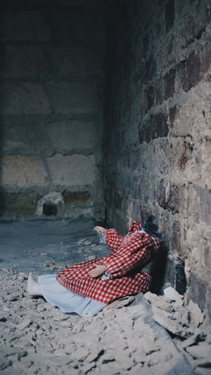 Headless doll by wall at abandoned place
